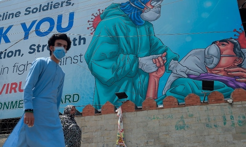 A man walks under a billboard that shows gratitude to frontline workers fighting against the spread of the Covid-19 in Rawalpindi on June 30.  —  AFP