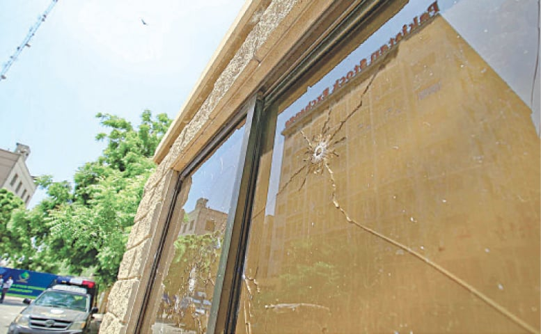 An outer windowpane can be seen damaged by a bullet in the ensuing exchange of fire.—INP