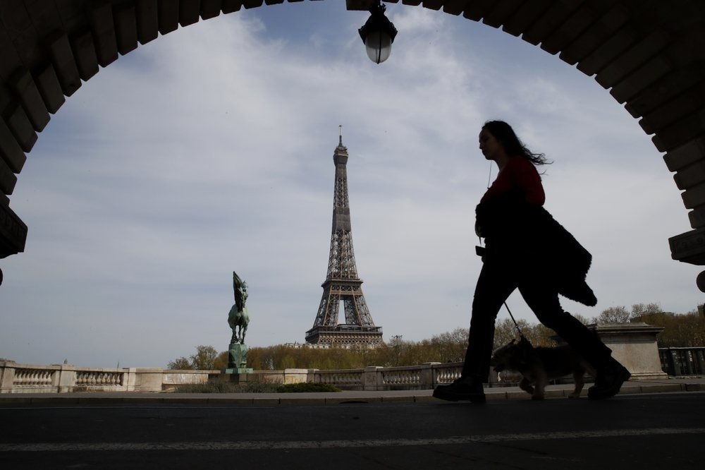 In this Tuesday, April 7, 2020 file photo, a woman walks her dog on a Paris bridge, with the Eiffel tower in background, during a nationwide confinement to counter the Covid-19. — AP