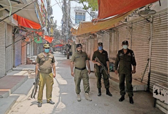 Policemen stand at the entry of Narankari Bazaar on Wednesday. — White Star