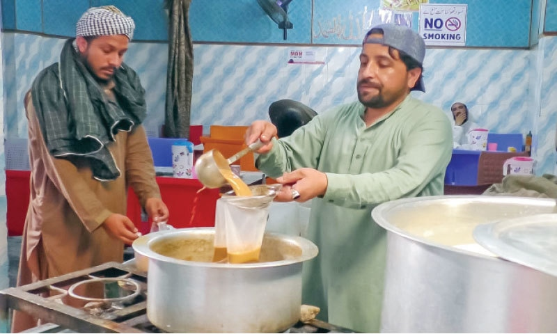 A man puts tea in a plastic bag for a customer at his outlet in Mingora. — Dawn