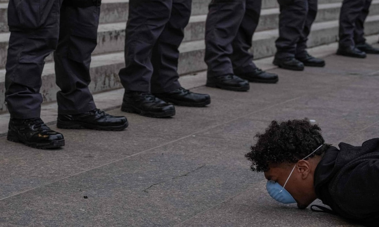 A protester holds a die-in in front of a row of police officers during a peaceful protest over the death of George Floyd, at the State Capital building in downtown Columbus, Ohio, on June 1. — AFP