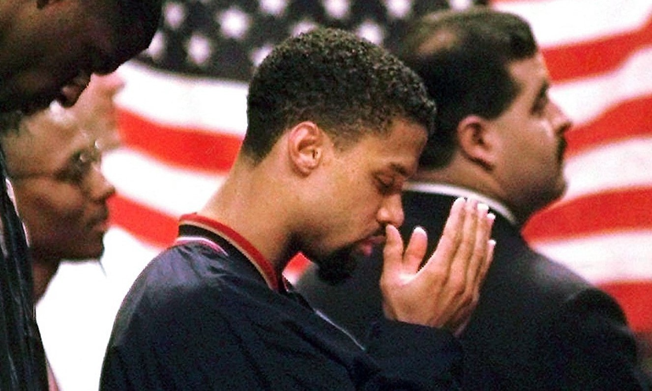 NBA player Mahmoud Abdul-Rauf stands with his teammates and prays during the national anthem before a basketball game. — AP/File
