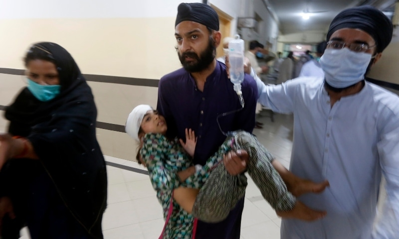People carry a girl who was injured in the accident after receiving initial treatment at a hospital in Sheikhupura. — AP