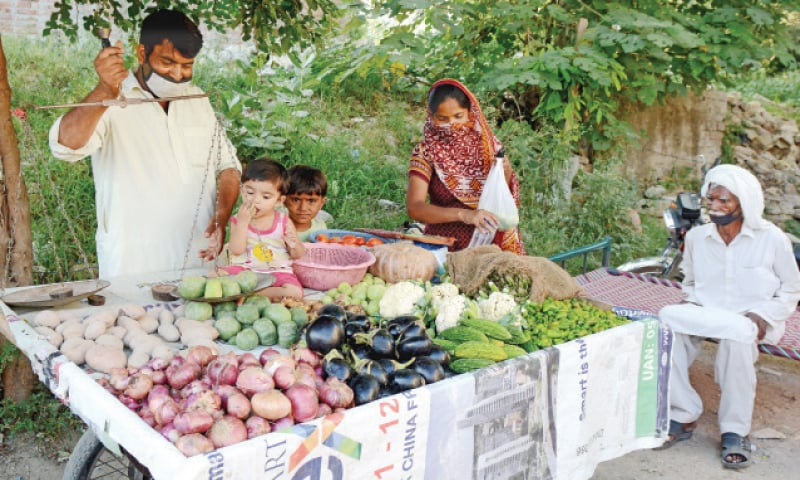 Health officials visit a slum in G-7 to test the residents for Covid-19. The other picture shows Razzaq Masih and his wife selling vegetables in the area. — White Star