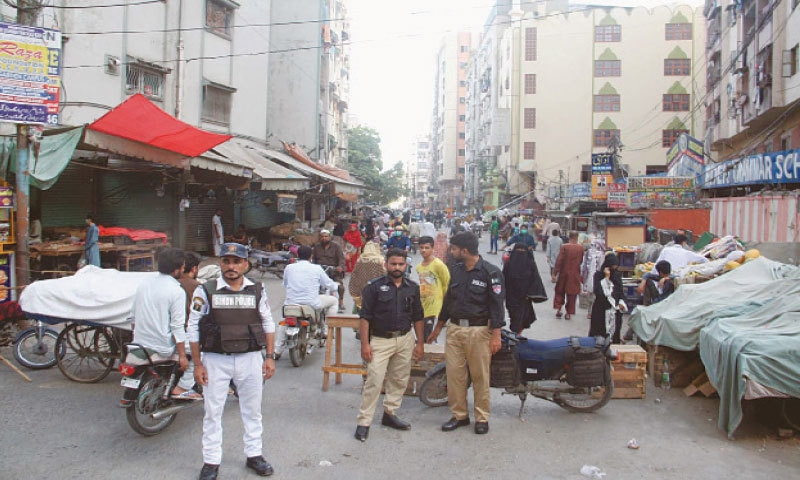 Policemen stand guard in a Garden neighbourhood on Friday where the 'smart' lockdown was extended for two weeks.—Online