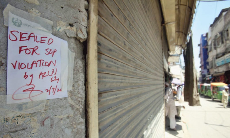 PESHAWAR: An official order is pasted on the wall of a shop in Karimpura bazaar, saying it has been sealed over violation of SOPs. All business activities in the city remained suspended on Friday because of smart lockdown.—PPI