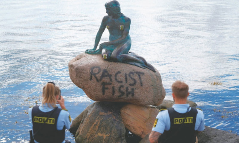 COPENHAGEN: Danish police officers take pictures of the base of the Little Mermaid statue after it was vandalised on Friday.—AFP