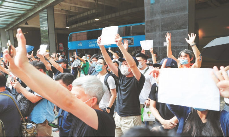 HONG KONG: Supporters raise white paper to avoid slogans banned under China's security law as they voice support for an arrested anti-law protester outside a court on Friday.—Reuters