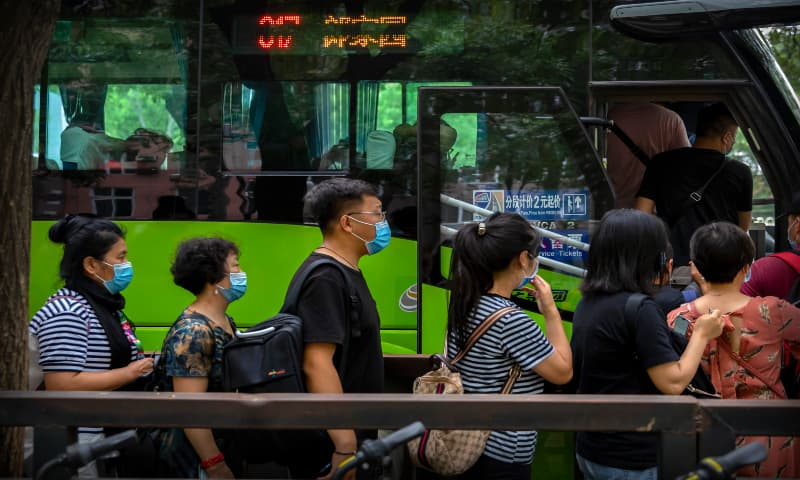 People wearing face masks to protect against the new coronavirus line up for a bus in Beijing on Friday, July 3, 2020. — AP