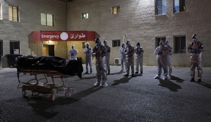 Health workers and people in protective suits pray before the body of a Palestinian woman who has died after contracting Covid-19, in Nablus, in the Israeli-occupied West Bank on July 5, 2020. — Reuters