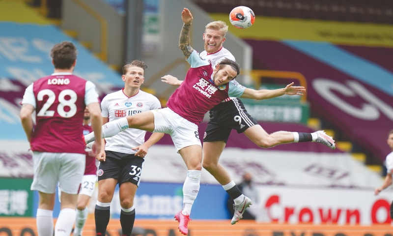 BURNLEY: Sheffield United's Oliver McBurnie (top) vies for the ball with Burnley's Josh Brownhill during their Premier League match at Turf Moor on Sunday.—AP