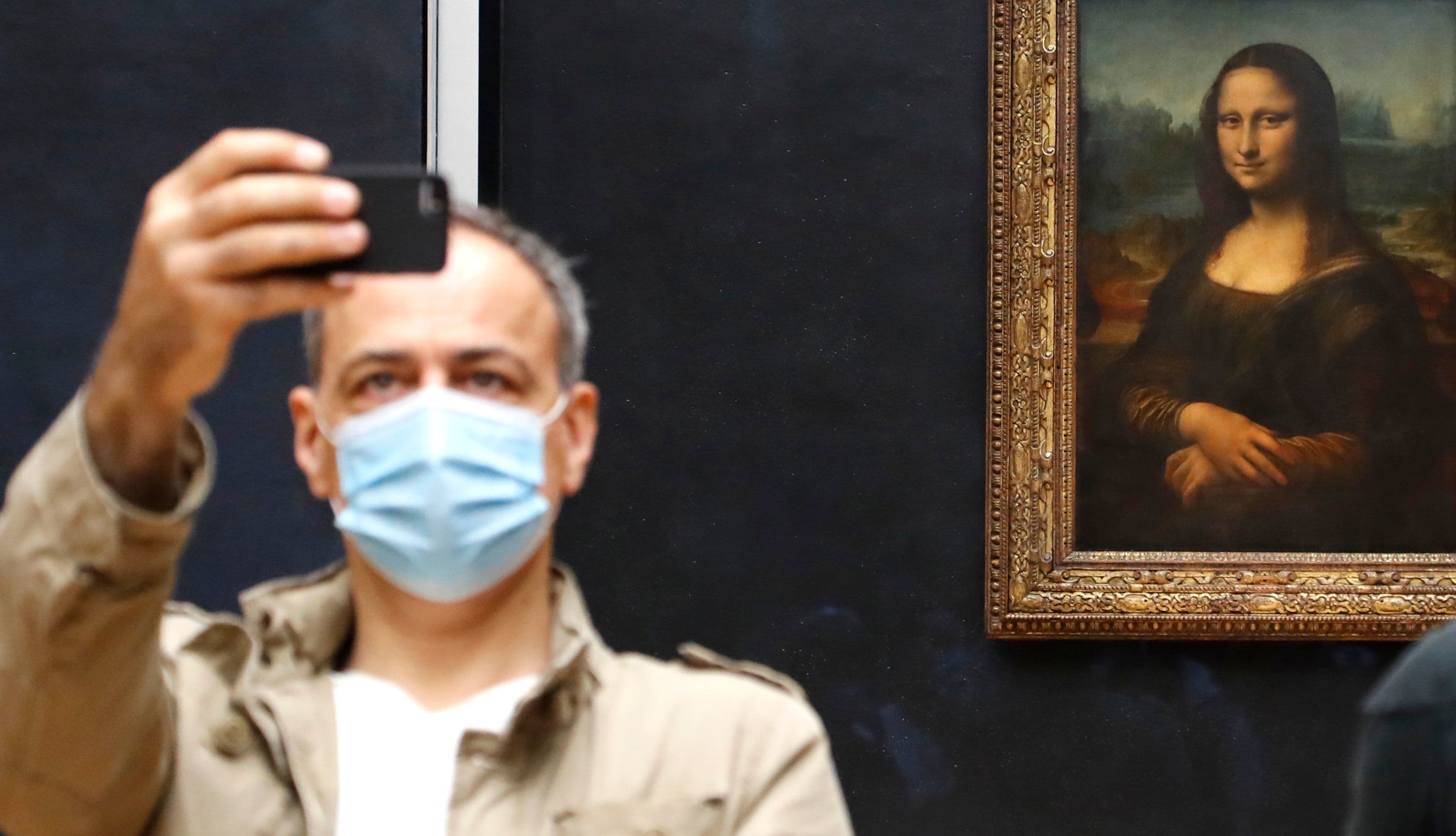 """A visitor wearing face mask takes a picture in front of Leonardo da Vinci's masterpiece """"Mona Lisa"""" also known as """"La Gioconda"""" at the Louvre Museum in Paris on July 6. — AFP"""