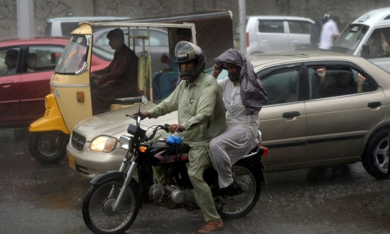 Commuters drive their vehicles on a street during rain showers in Karachi on July 6. — AFP