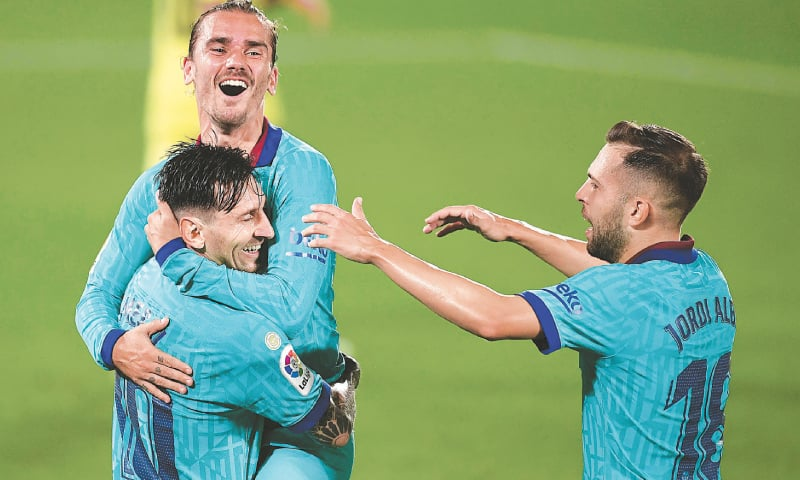 VILLARREAL: Barcelona's Antoine Griezmann (top) celebrates with team-mates Lionel Messi and Jordi Alba (R) after scoring during the La Liga match against Villarreal at the Madrigal Stadium.—AFP