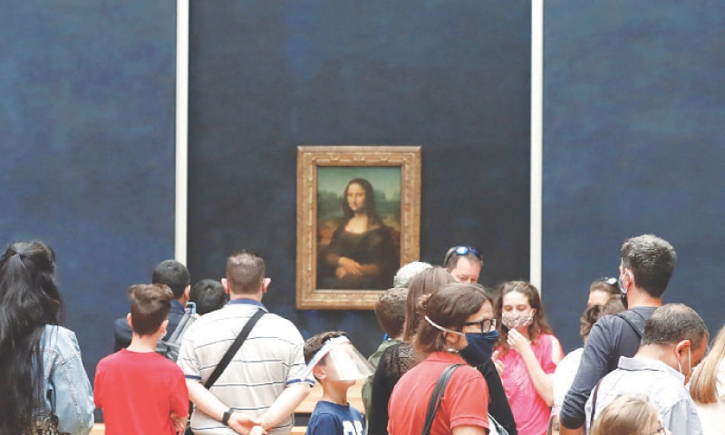 PARIS: Visitors wearing masks gather in front of Leonardo da Vinci's masterpiece 'Mona Lisa' at the Louvre Museum on Monday. The museum reopened its doors after months of closure due to lockdown measures linked to the novel coronavirus. The crisis has already caused more than 40 million euros in losses at the Louvre.—AFP