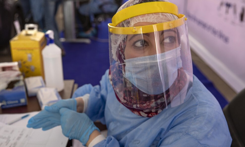 In this June 17, 2020 file photo, a health worker wearing protective gear prepares to take swab samples from people lining up in their cars to test for the coronavirus at a drive-through Covid-19 screening center at Ain Shams University in Cairo, Egypt. — AP/File