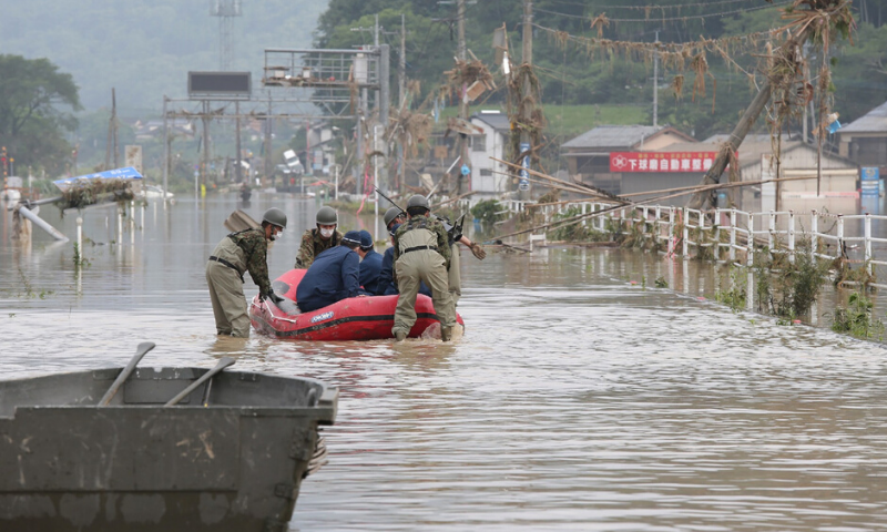 Japan Self-Defense Forces and police officers handle an inflatable boat to join rescue operations at a nursing home following heavy rain in Kuma village, Kumamoto prefecture, on Sunday. — AFP/File