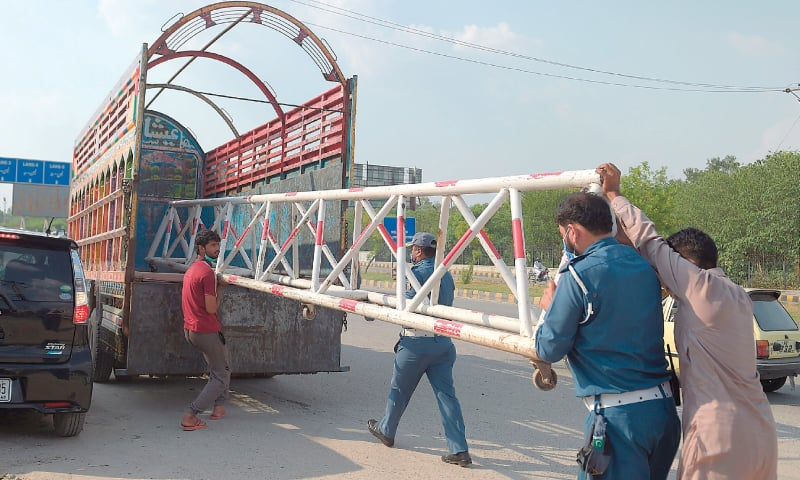RAWALPINDI: Traffic policemen shift a road blocker to reopen a road on Tuesday after it was sealed by authorities as a preventive measure against Covid-19.—AFP