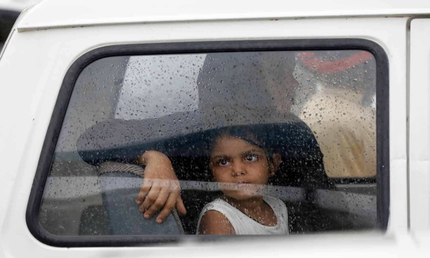 A girl looks out of a car window with raindrops during the season's first monsoon rain in Karachi on July 6. — Reuters
