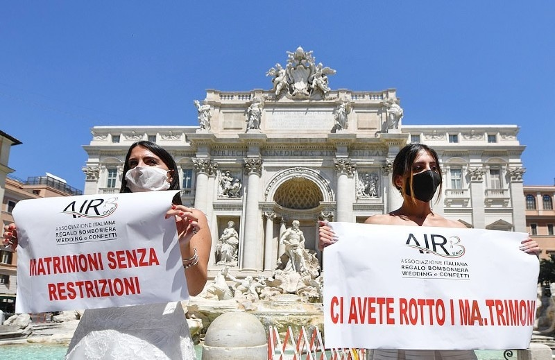 عروسی لباس میں ملبوس لڑکیوں نے تریوی فاؤنٹین کی تاریخی عمارت کے باہر مظاہرہ کیا—فوٹو: اے ایف پی