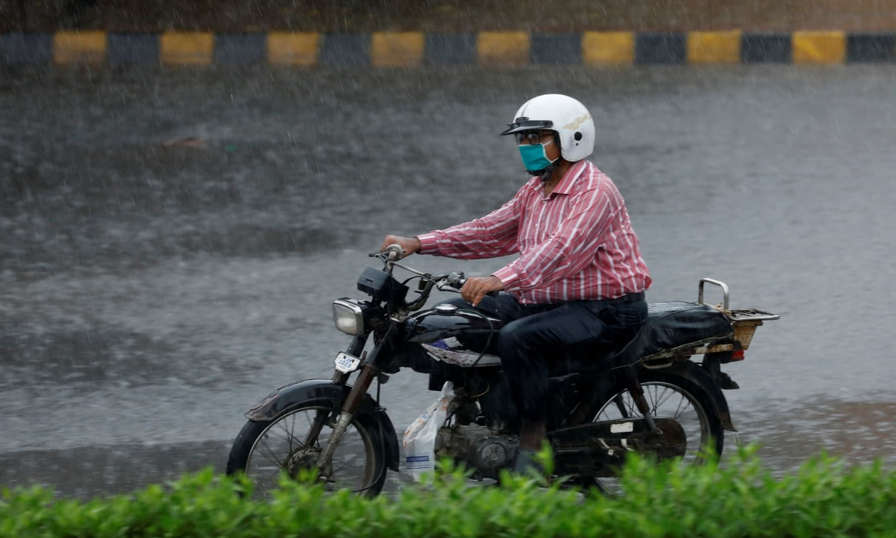 A man wearing a protective mask rides a motorcycle during the season's first monsoon rain in Karachi on July 6. — Reuters