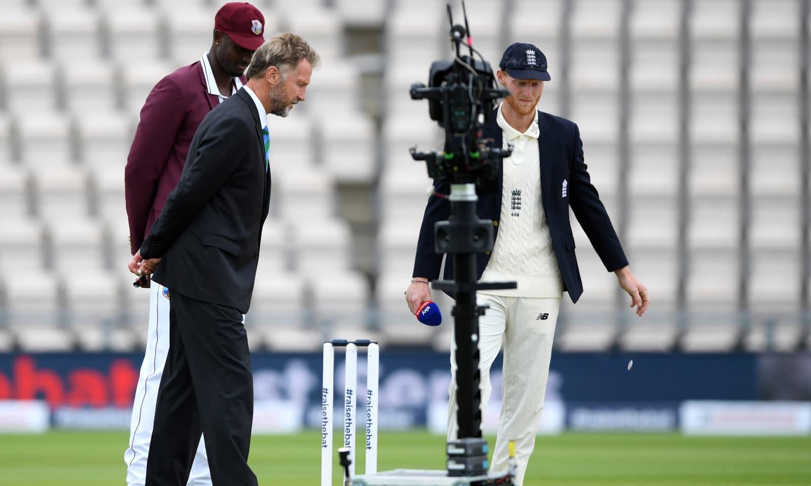 انگلینڈ اور ویسٹ انڈیز کے کپتان ٹاس کے موقع پر سکے کو دیکھ رہے ہیں — فوٹو: رائٹرز