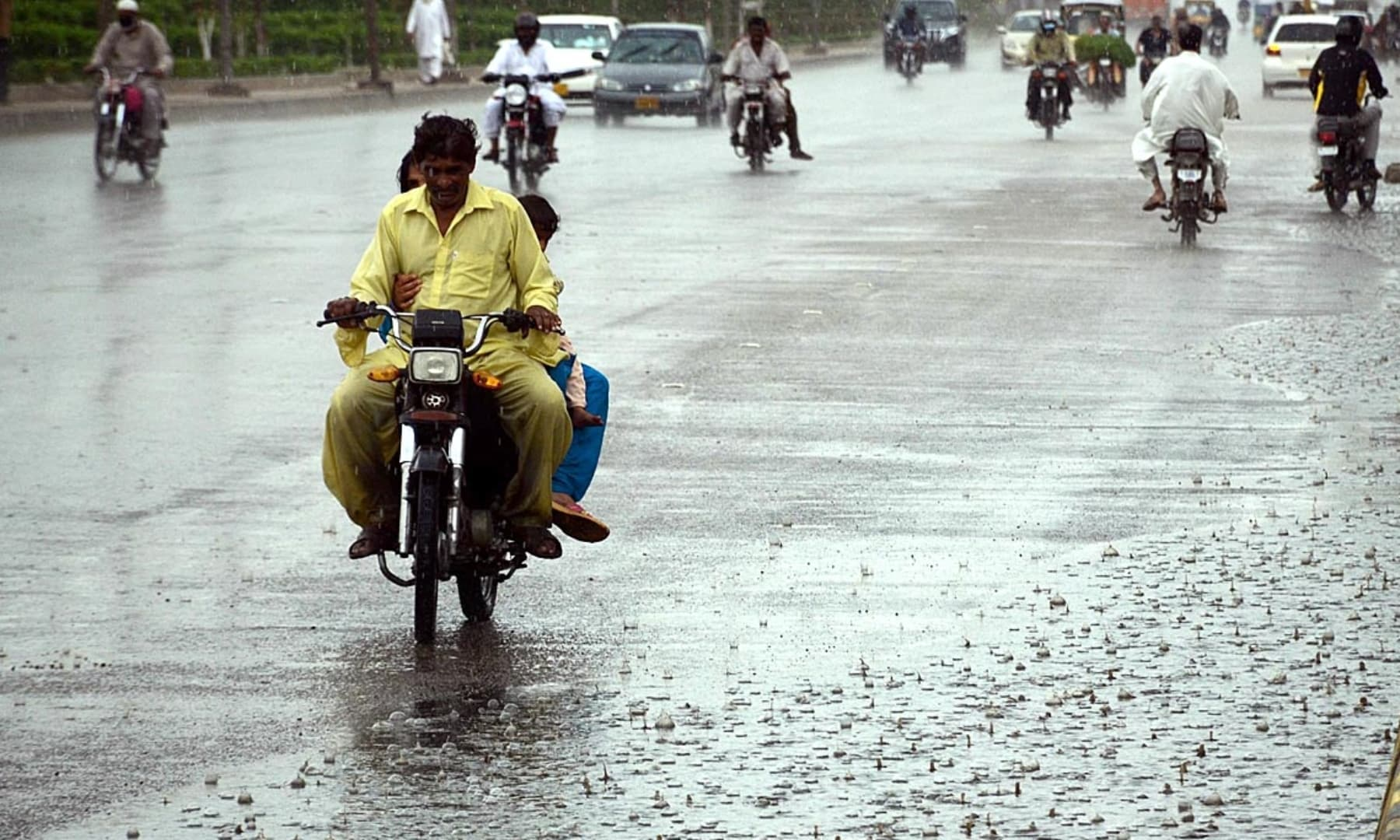 Vehicles on the road during rain in Karachi on Wednesday. — APP