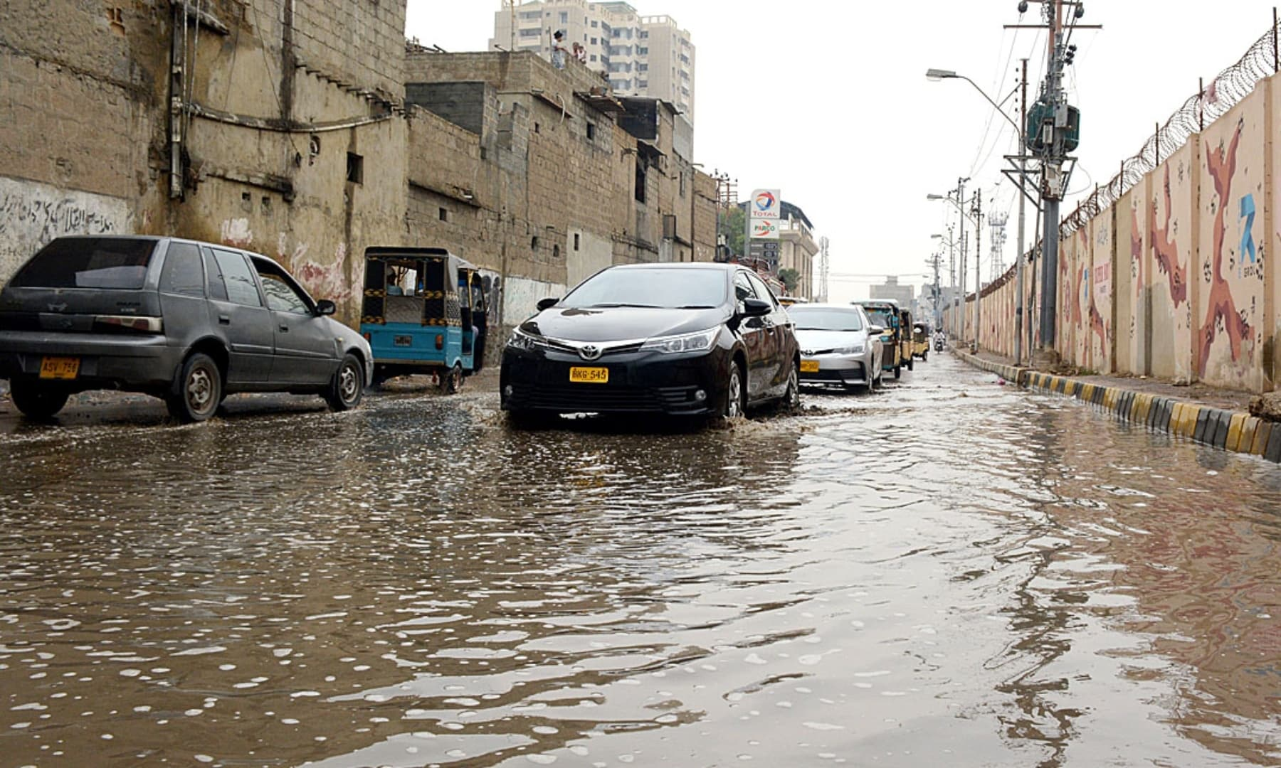 Vehicles pass through stagnant water accumulated near Kala Pul after rain in Karachi. — APP