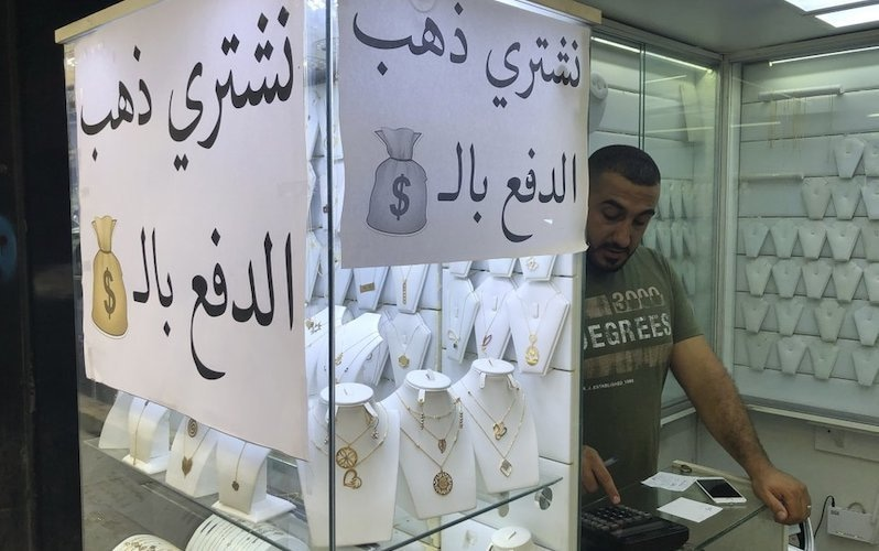"""A man works in a jewellery store where an Arabic sign reads, """"We buy gold and pay in dollars,"""" in Beirut, Lebanon, on Monday, July 6, 2020. — AP"""
