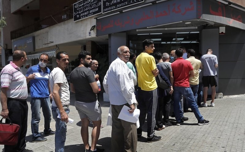 People line up outside an exchange shop to buy US dollars, in Beirut, Lebanon, June 17, 2020. — AP