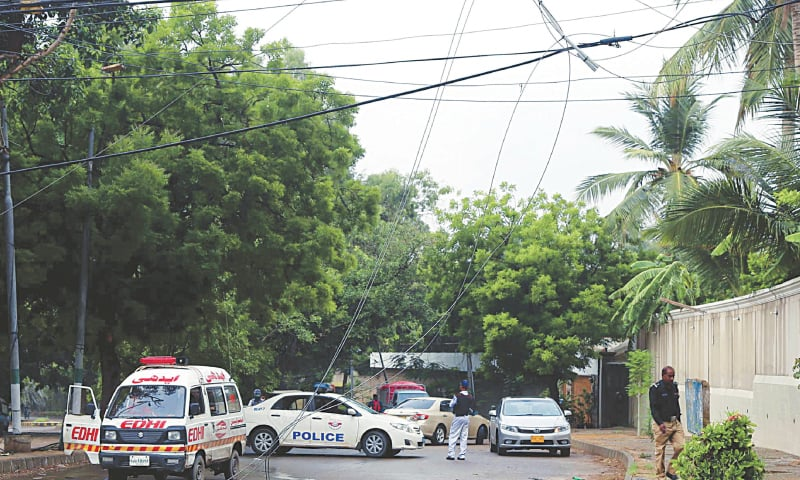 THE snapped live electric wires are yet to be taken care of as police and an ambulance arrive at the site in the  Karsaz area where an unsuspecting motorcyclist was electrocuted on Wednesday.—PPI