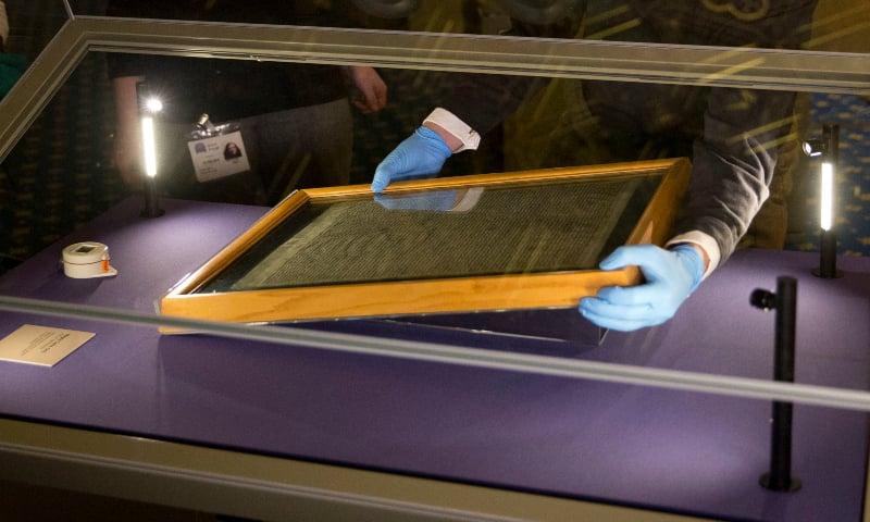 The Salisbury Cathedral 1215 copy of the Magna Carta is installed in a cabinet by Chris Woods, right, the director of the National Conservation Service to be displayed alongside the other three surviving original parchment engrossments of the Magna Carta to mark the 800th anniversary of the sealing of Magna Carta at Runnymede in 1215, in the Queen's Robing Room at the Houses of Parliament in London on February 5, 2015.  — AP