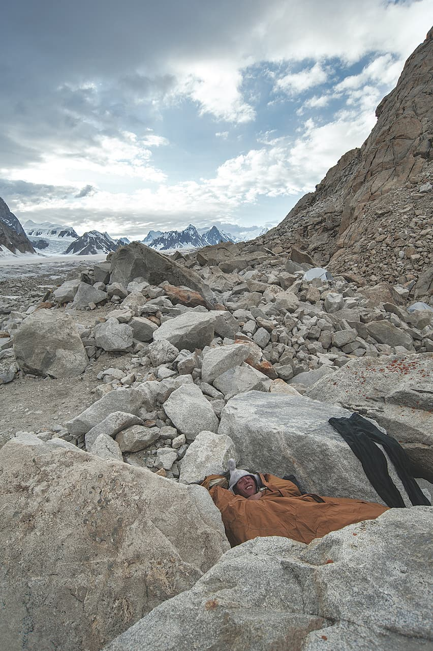 A porter sleeping among the rocks during a trekking expedition | Nadir Toosy