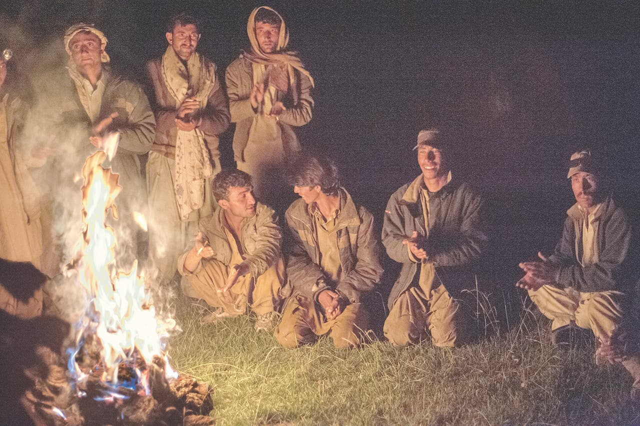 Porters gather by a campfire during an expedition before the lockdown | Nadir Toosy