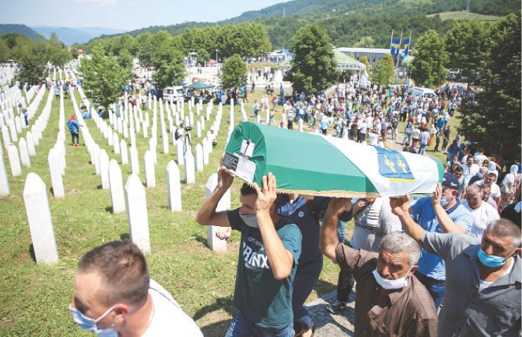 Srebrenica: Men carry a coffin at a graveyard during a mass funeral in Potocari near here on Saturday. Bosnia marks the 25th anniversary of the massacre of more than 8,000 Bosnian Muslims, with many relatives unable to attend due to the coronavirus.—Reuters
