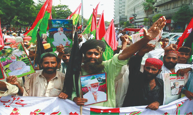 Supporters of the Jamhoori Watan Party hold pictures of their leader, tribal chieftain Nawab Akbar Bugti, as they protest in Karachi on the second anniversary of his death | Reuters