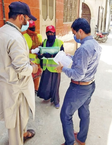 Officials inspect presence of larva in a dengue high-risk area in Taxila on Sunday. — Dawn