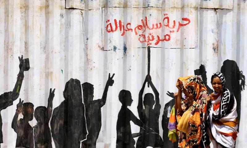 "Civilians walk past graffiti reading in Arabic ""Freedom, Peace, Justice and Civilian"" in the Burri district of Khartoum. — Reuters/File"