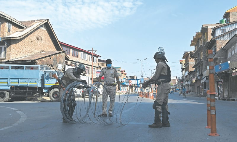 SRINAGAR: Indian paramilitary troops block a road during a lockdown imposed after a surge of Covid-19 cases on Monday.—AFP