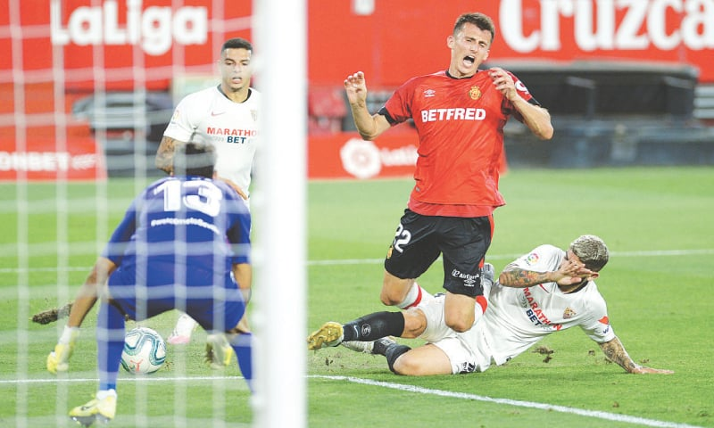 SEVILLE: Sevilla's Ever Banega (R) tackles Real Mallorca's Ante Budimir during their La Liga match at the Ramon Sanchez Pizjuan Stadium.—AFP
