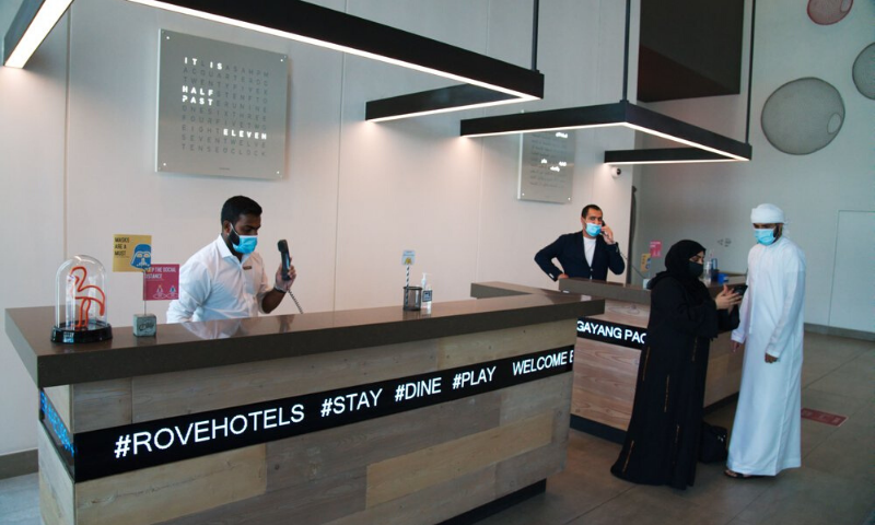 In this July 6, 2020 file photo, the front desk staff wearing masks due to the coronavirus pandemic help customers at the Rove City Centre Hotel in Dubai, United Arab Emirates. — AP