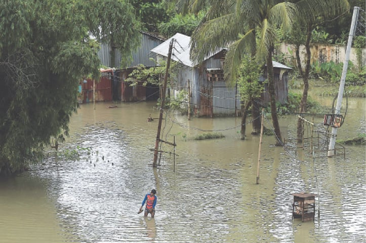 A MAN walks through floodwaters in Sunamgong, Bangladesh, on Tuesday. Almost four million people have been hit by monsoon rains in South Asia, with a third of Bangladesh under water.—AFP