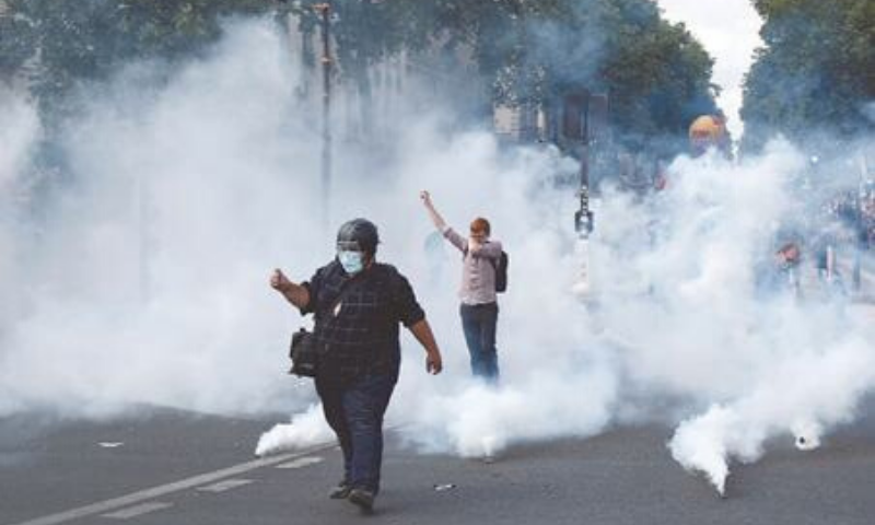 Paris: Protesters gesture amid smoke from tear gas during a demonstration on Tuesday as part of a nationwide day of protests by health workers to demand better work conditions. — AFP