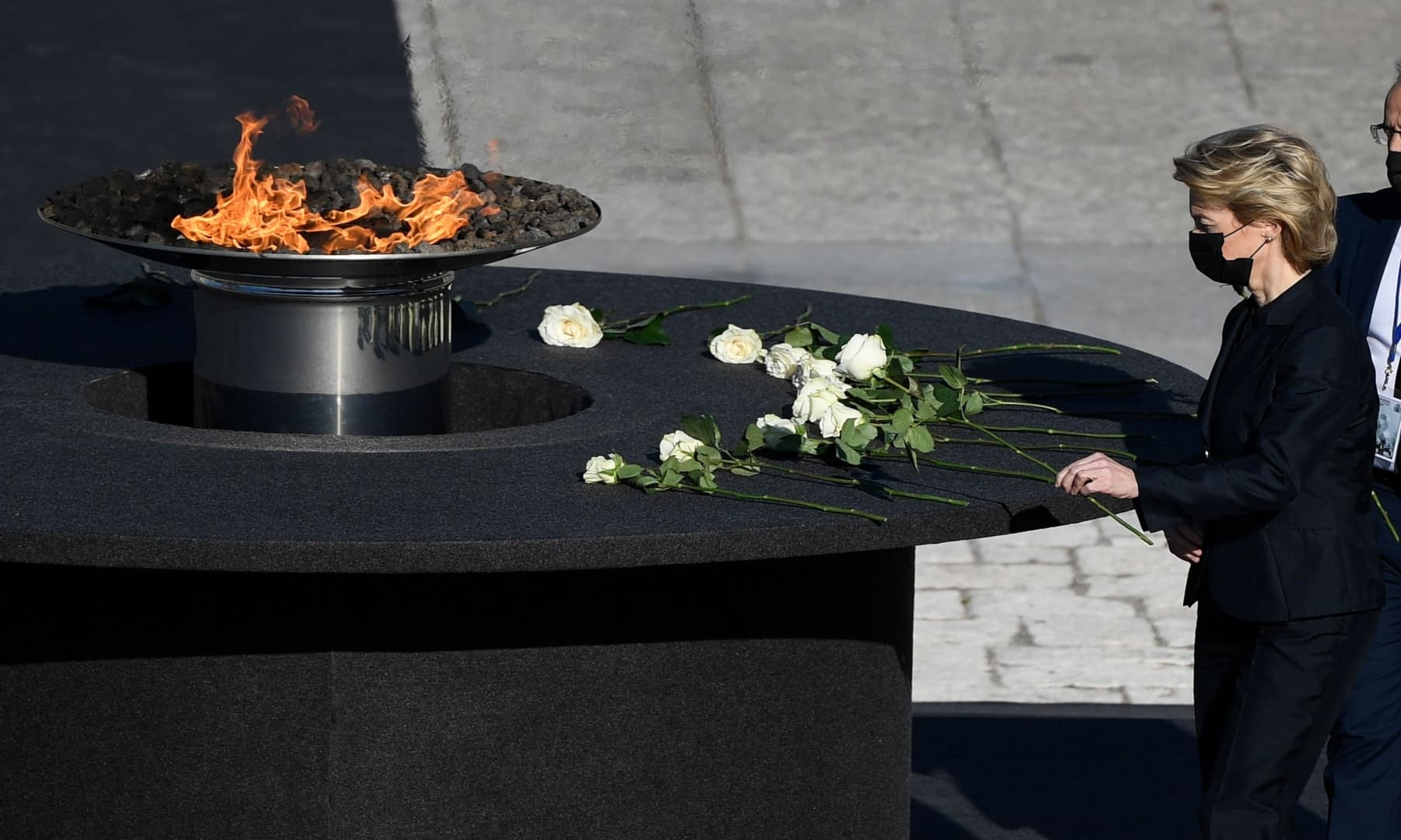President of the European Commision Ursula von der Leyen leaves a rose next to a cauldron during a state ceremony to honour the 28,400 victims of Covid-19 as well as those public servants who have been fighting on the front line against the pandemic in Spain. — AFP