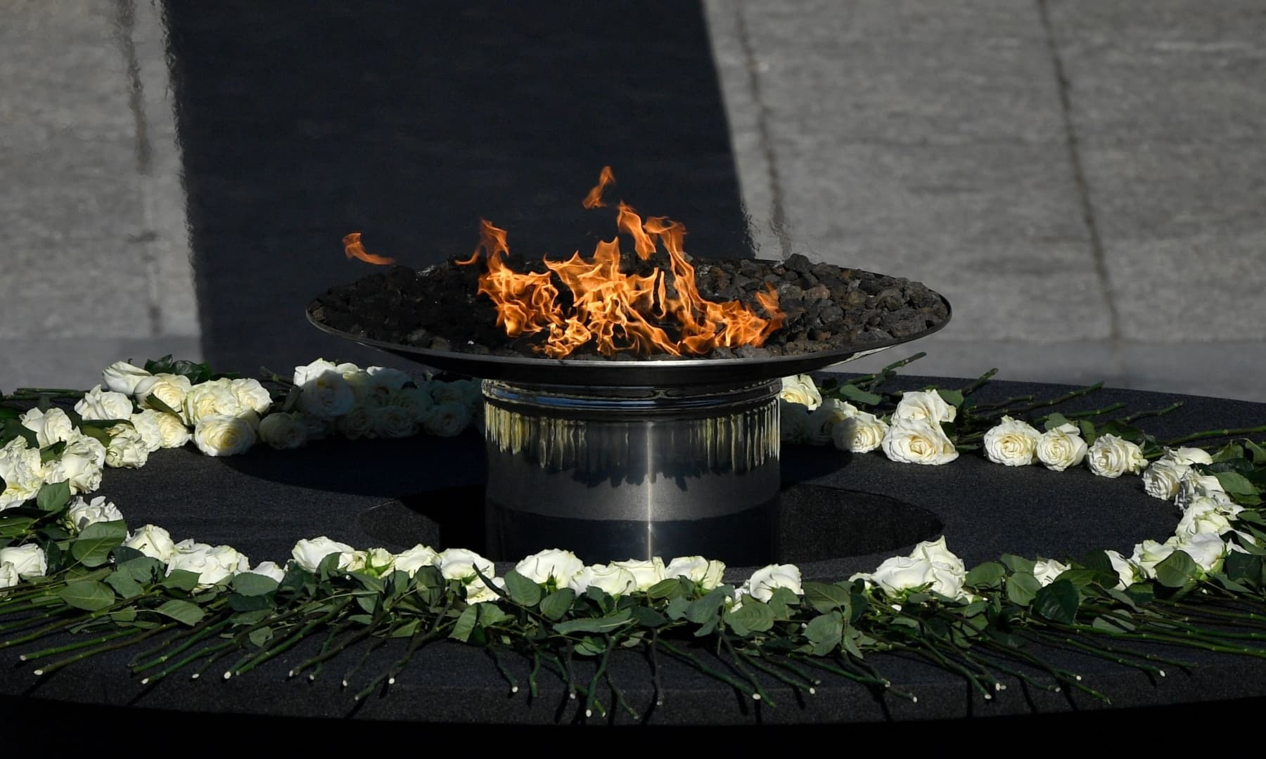 A flame burns on a cauldron surrounded by white roses during a state ceremony to honour the 28,400 victims of the coronavirus crisis as well as those public servants who have been fighting on the front line against the pandemic in Spain. — AFP