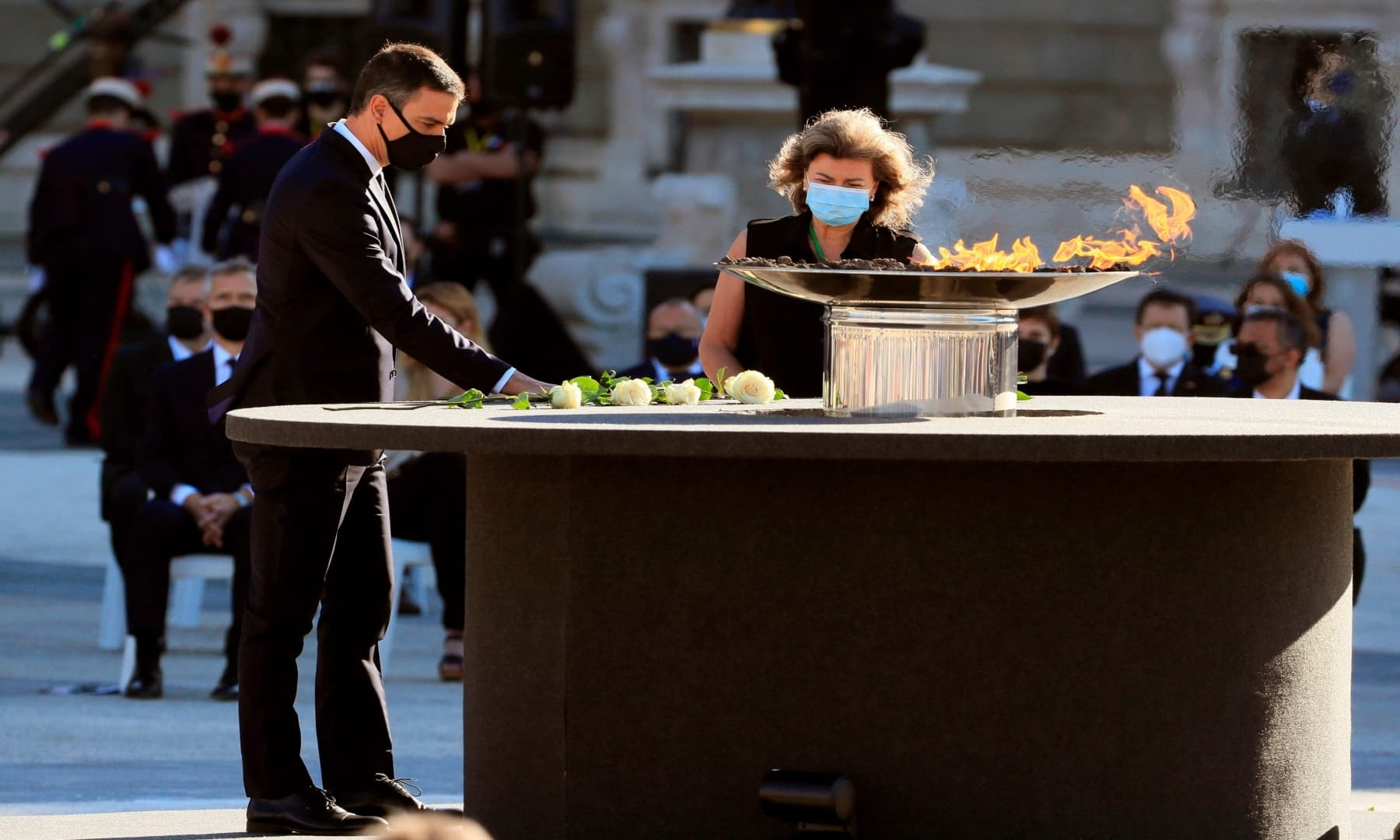 Spanish Prime Minister, Pedro Sanchez (L) leaves a white rose next to a cauldron during a state ceremony to honour the victims of the coronavirus crisis. — AFP