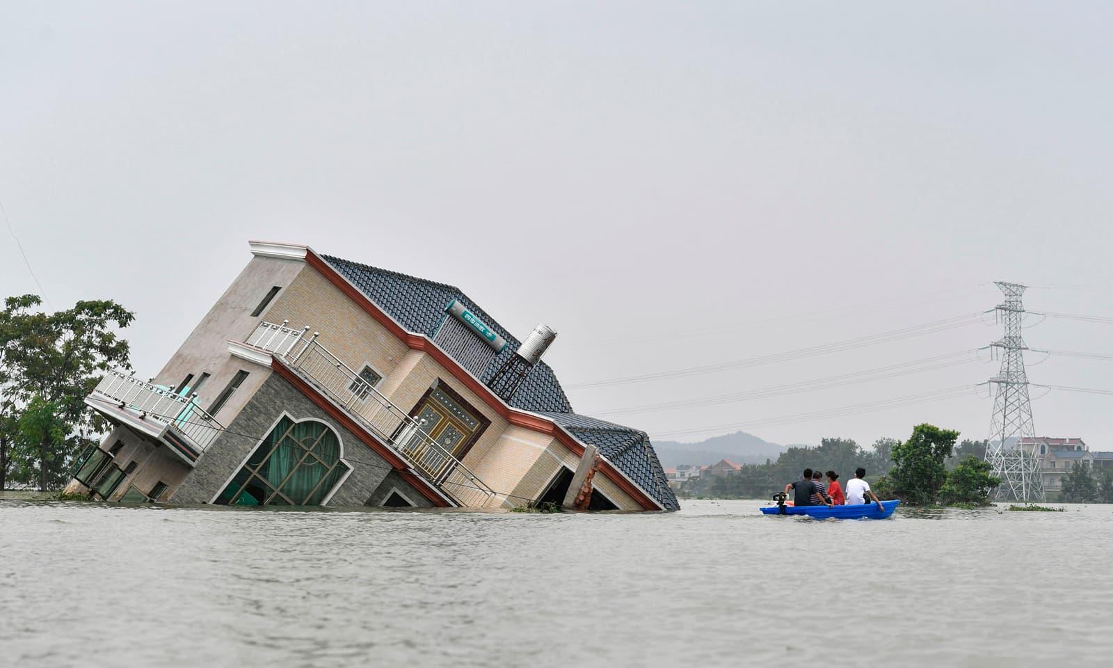 چین کے وسطی صوبے جیان ژن میں سیلاب کے باعث ڈوبتا ہوا مکان — فوٹو: اے ایف پی