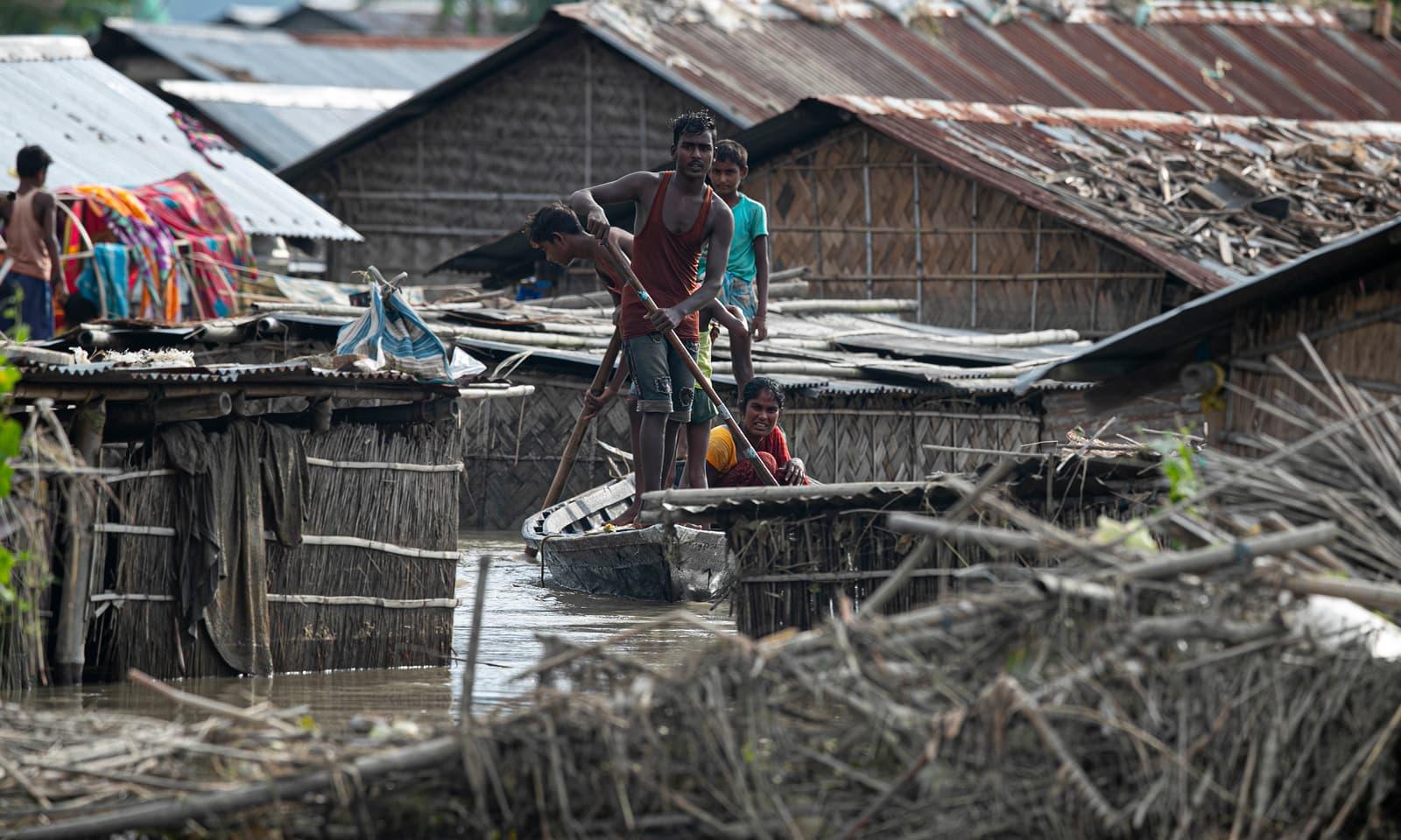 بھارتی ریاست آسام کے ضلع موری گاؤں میں کشتی پر سوار ایک خاندان پانی میں نیم غرق مکانوں کے پاس سے گزر رہا ہے— فوٹو: اے پی