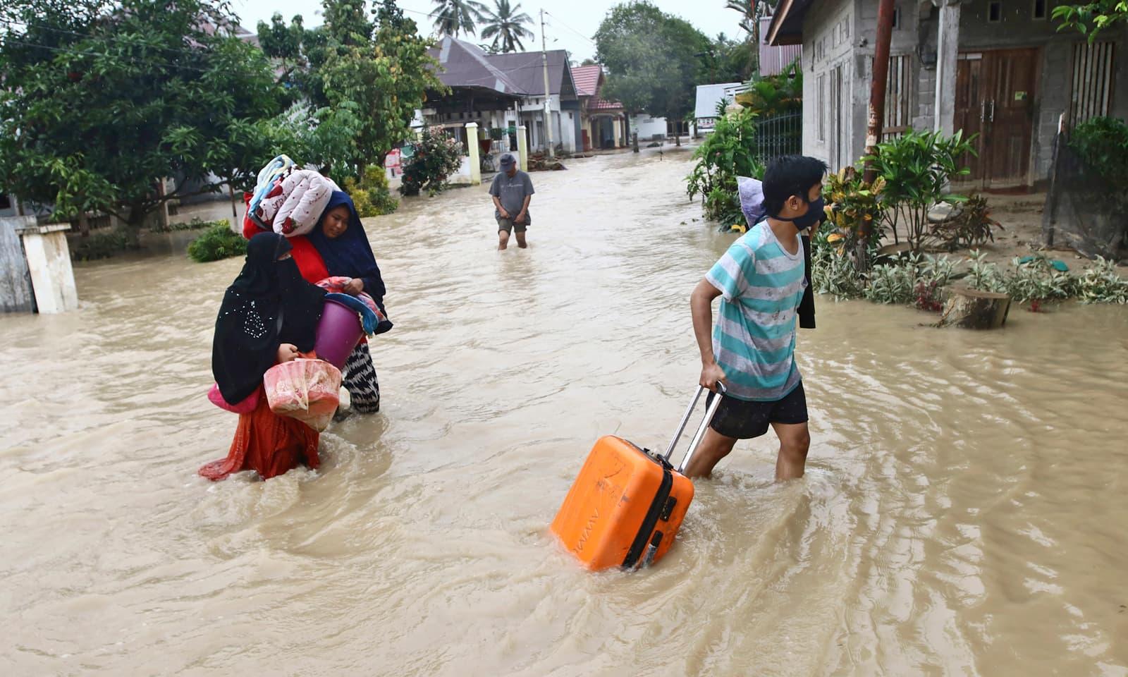 انڈونیشیا کے صوبے سلاسیوی میں لوگ ضروری سامان لے کر نقل مکانی کر رہے ہیں— فوٹو: اے پی